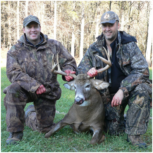 Two hunters showing their trophy after a day of whitetail deer hunting